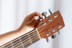 Photo of girl`s hand tuning acoustic guitar, close-up. Photo of girl`s hand tuning guitar, close-up Royalty Free Stock Photo