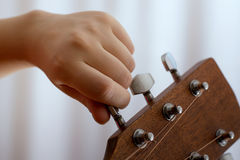 Photo of girl`s hand tuning acoustic guitar, close-up. Photo of girl`s hand tuning guitar, close-up Stock Images