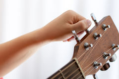 Photo of girl`s hand tuning acoustic guitar, close-up. Photo of girl`s hand tuning guitar, close-up Stock Photography