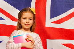 Photo of girl with textbooks against English flag Royalty Free Stock Photos