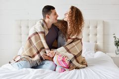 Photo of girlfriend and boyfriend dressed casually, enjoy coziness under plaid in bedroom, embrace each other, look into eyes and stock photography
