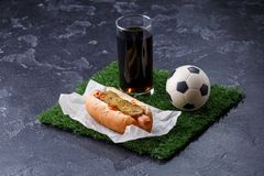 Photo of glass of beer, green grass with soccer ball, hotdog royalty free stock image