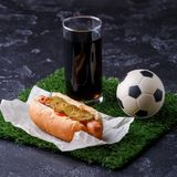 Photo of glass of beer, green grass with soccer ball, hotdog royalty free stock images