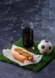 Photo of glass of beer, green grass with soccer ball, hotdog stock photography