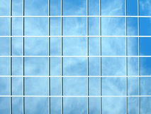 Photo of a glass building. With clouds reflecting in the windows Stock Image
