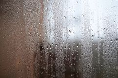 A photo of the glass surface of the window, covered with a multitude of droplets of various sizes. Background texture of a dense l. Ayer of condensate on glass Stock Photo