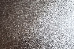 A photo of the glass surface of the window, covered with a multitude of droplets of various sizes. Background texture of a dense l. Ayer of condensate on glass Royalty Free Stock Photography