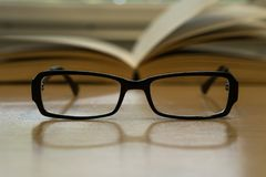 Photo of glasses and opened book behind them, reading concept. Closeup photo of glasses and opened book behind them, reading concept royalty free stock photography