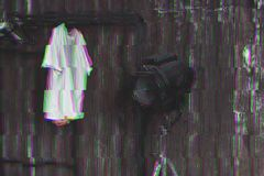 Photo with glitch effect. Design of loft Interior of dressing room. Metal wall and cinema lightning and white t-shirt on Royalty Free Stock Photography