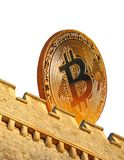 Digital bitcoin moneybox. Photo of a gold bitcoin cryptocurrency being deposited in a castle moneybox Royalty Free Stock Photo
