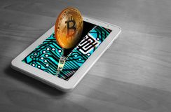 Bitcoin digital cryptocurrency gold coin. Photo of a gold bitcoin cryptocurrency digital coin emerging from a tablet device with printed circuit board design Stock Images