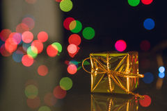 Photo of gold gift box with bokeh lights on black background.  Royalty Free Stock Photo