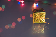 Photo of gold gift box with bokeh lights on black background.  Stock Images
