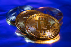 Photo Golden Bitcoins new virtual money Close-up on a blue background. Photo Stock Photography