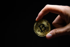Woman`s hand holding golden Bitcoin on black background Stock Photo