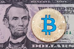 Photo of golden ccruptocurrency blue bitcoin on dollar banknote Stock Images