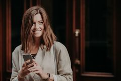 Photo of good looking woman searches information, uses cell phone, dressed in elegant jacket, poses against door background, looks royalty free stock photo