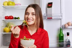 Photo of good looking young woman with pleasant appearance stands near opened refrigerator with bowl of salad, eats only healthy f Stock Photo
