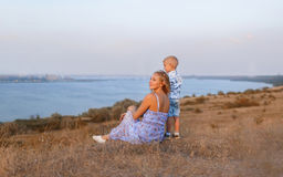 A cute boy and his mother on a river background. A happy family together enjoying a beautiful nature. Copy space. A photo of a gorgeous mother and her handsome Stock Photography