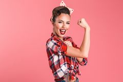 Gorgeous strong young pin-up woman showing biceps. Photo of gorgeous strong young pin-up woman isolated over pink background wall showing biceps royalty free stock photography