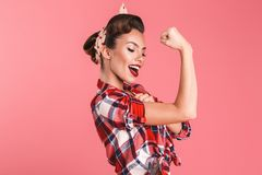 Gorgeous strong young pin-up woman showing biceps. stock photography