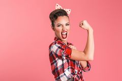 Gorgeous strong young pin-up woman showing biceps. Photo of gorgeous strong young pin-up woman over pink background wall showing biceps screaming royalty free stock photography