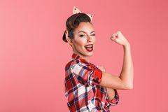 Gorgeous strong young pin-up woman showing biceps. Photo of gorgeous strong young pin-up woman over pink background wall showing biceps winking stock photography