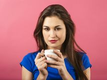Pretty woman drinking coffee. Photo of a gorgeous young woman drinking coffee over a pink background Stock Images