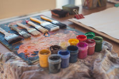 Photo of gouache and watercolor with brushes set in art studio. Oil paints smeared on palette Royalty Free Stock Photos