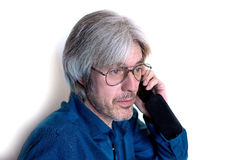 Photo gray-haired man with a short beard with glasses and mobile phone in his hand. A man talking on a cell phone. Photo gray-haired man with a short beard and Royalty Free Stock Image