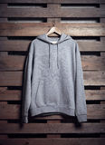 Photo of gray hoody holding on wood background. Vertical blank mockup Royalty Free Stock Photography