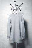 Photo of gray sweatshirt hanging on the hanger. Vertical Royalty Free Stock Image