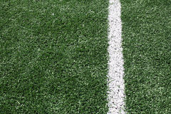Photo of a green synthetic grass sports field with white line Stock Photos