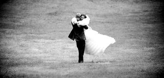 Photo of groom lifting bride and spinning her Stock Photography