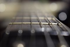 A photo of a guitar neck with strings and a wood texture - the material of a guitar neck. Selective focus on one guitar threshold. Music background royalty free stock images