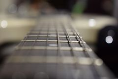 A photo of a guitar neck with strings and a wood texture - the material of a guitar neck. Selective focus on one guitar threshold. Music background royalty free stock photos