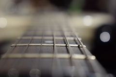 A photo of a guitar neck with strings and a wood texture - the material of a guitar neck. Selective focus on one guitar threshold stock image