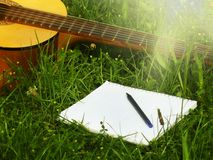 Photo guitar and notepad with pen on the grass Stock Photo