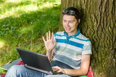 Photo of guy with laptop and in headphones. Sitting under tree on summer lawn Royalty Free Stock Photography