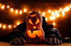 Photo of halloween background with pumpkin and witch hands. On wooden table against grunge bokeh lights background Royalty Free Stock Photography