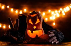 Photo of halloween background with pumpkin and witch hands. On wooden table against grunge bokeh lights background Royalty Free Stock Images