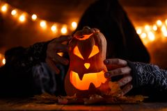 Photo of halloween pumpkin cut in shape of face with witch. On background with burning yellow lights Stock Images