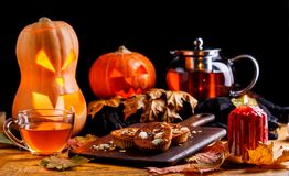 Photo of halloween pumpkins, cakes, cup of tea. On black background Stock Photo