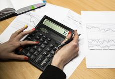 Photo of hands holding the pen and pressing the calculator buttons above the documents stock image
