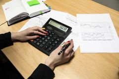 Photo of hands holding the pen and pressing the calculator buttons above the documents stock images