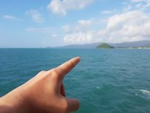 Photo of hand pointing finger into distance of sea coast, cloudy sky Stock Photography