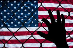 A symbolic representation of immigrants and the united states of america. A photo of a hand reaching but unable to get to America Royalty Free Stock Photography