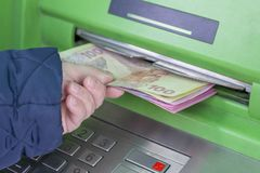 Photo of hand taking from ATM Ukrainian hryvnas royalty free stock photos