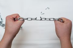 Photo of hands holding a broken chain. Photo of hands holding a broken mettalic chain stock images