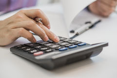 Photo of hands holding pencil and pressing calculator buttons over documents.  Royalty Free Stock Photo